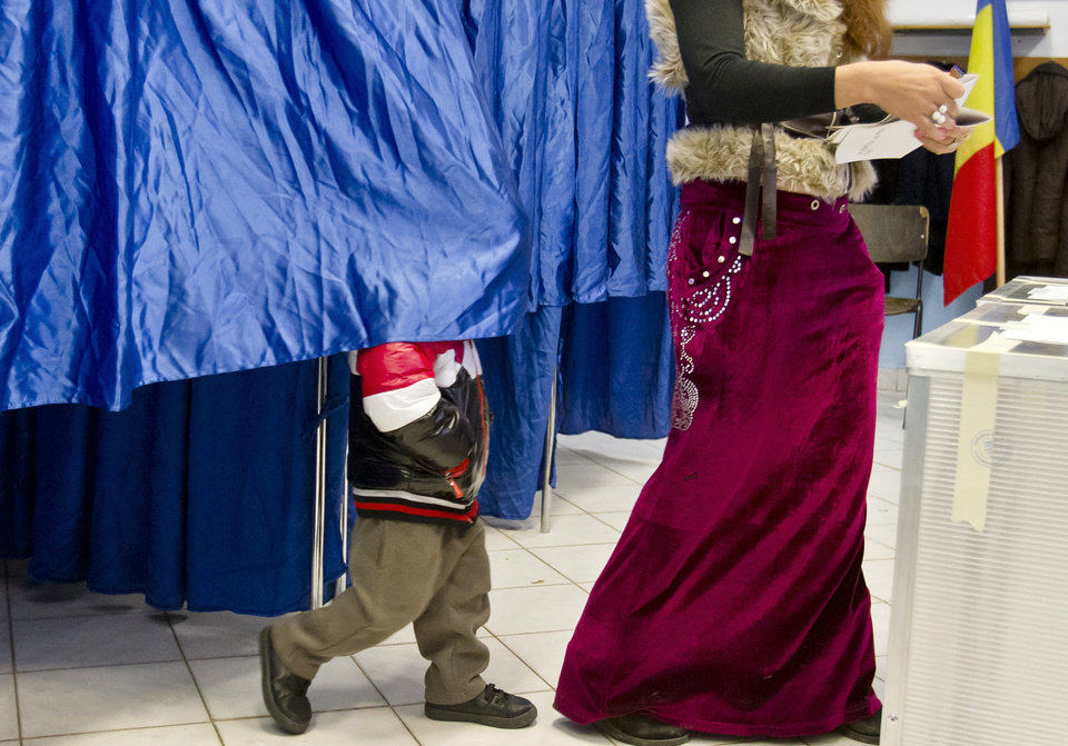 A woman is followed by a child as she exits a voting cabin on the outskirts of Bucharest, Romania, Sunday, Dec. 9, 2012. Millions of Romanians braved rain and snow Sunday as they went to the polls for a parliamentary election that center-left government is expected to win, but the result could lead to more of the political instability that has plagued the impoverished Balkan nation this year. (AP Photo/Vadim Ghirda)