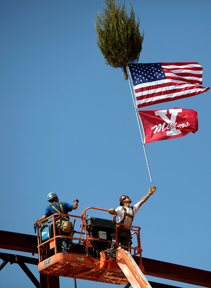 Aaron East, (left) and Dave Kaschmitter, Ironworkers with All Steel, put up flags and a tree during a topping out ceremony at the new Yukon High School still under construction in Yukon, Okla., on Tuesday, August 31, 2010. Photo by John Clanton, The Oklahoman