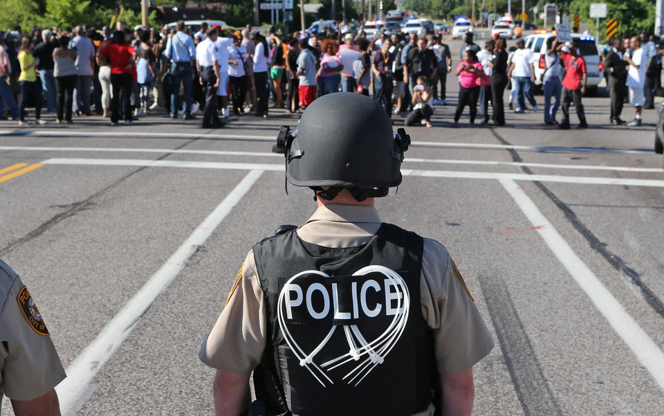 Photo - A line of police wait for demostrators at Canfield Avenue after they had walked down W. Florissant in Ferguson, Mo. on Wednesday, Aug. 13, 2014. On Saturday, Aug. 9, 2014, a white police officer fatally shot Michael Brown, an unarmed black teenager, in the St. Louis suburb. (AP Photo/St. Louis Post-Dispatch, J.B. Forbes)