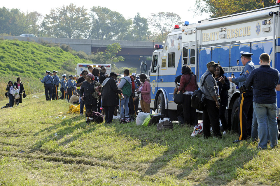 Photo -   Passengers wait after their bus overturned in a ditch at an exit ramp off Route 80 in Wayne, N.J. Saturday, Oct. 6, 2012. The chartered tour bus from Toronto carrying about 60 people overturned on an interstate exit ramp. Three people have been taken to hospital with non-life-threatening injuries. (AP Photo/Bill Kostroun)