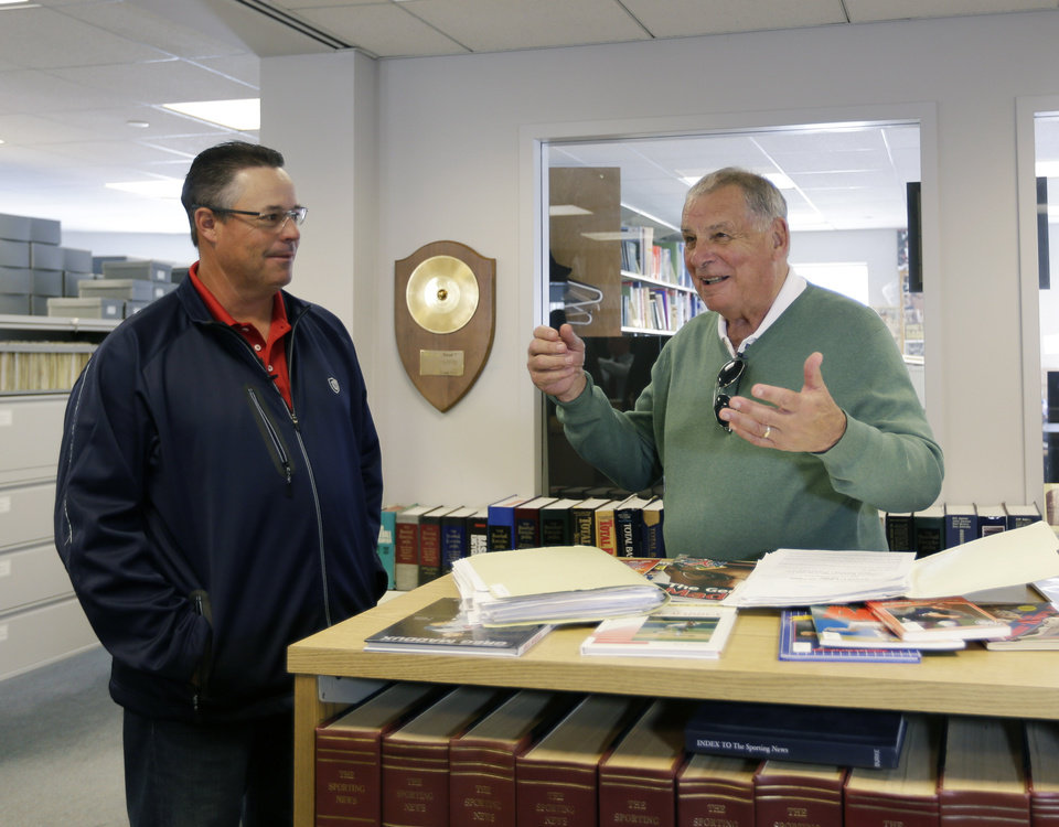Photo - Former Atlanta Braves pitcher Greg Maddux, left, and former manager Bobby Cox talk in the library during their orientation visit at the Baseball Hall of Fame on Monday, March 24, 2014, in Cooperstown, N.Y. They will be inducted to the hall in July. (AP Photo/Mike Groll)