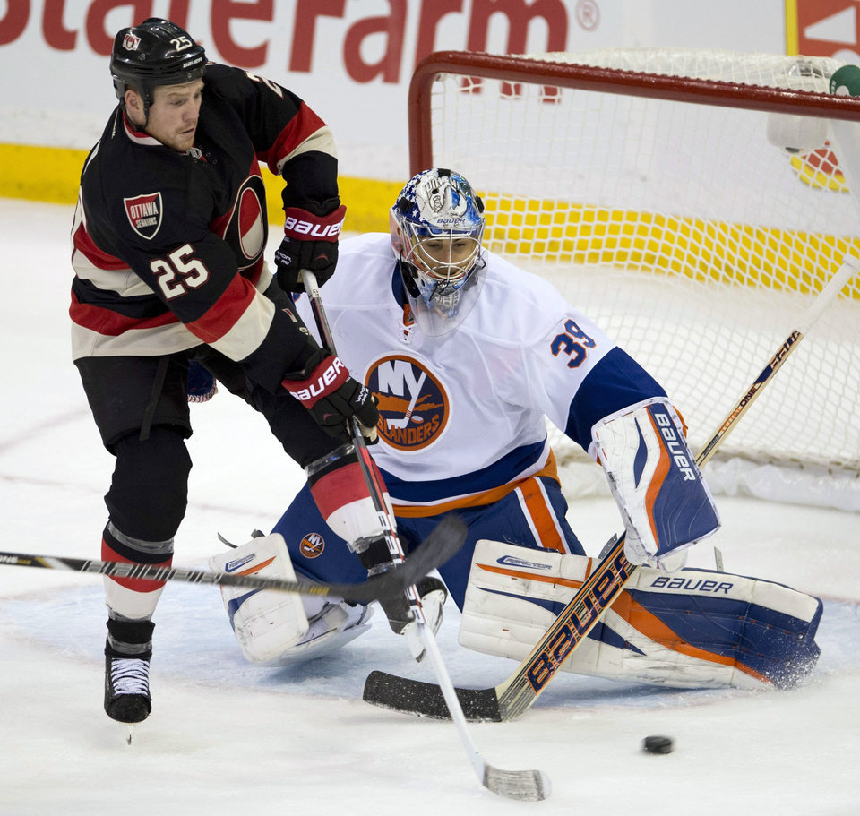 Ottawa Senators right wing Chris Neil tries to tip the puck past New York Islanders goalie Rick DiPietro during the second period of an NHL hockey game in Ottawa, Ontario, Tuesday, Feb. 19, 2013. (AP Photo/The Canadian Press, Adrian Wyld)