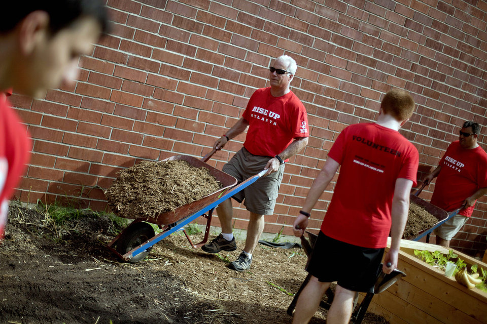 Photo -   Atlanta Falcons head coach Mike Smith, second from left, pushes a wheelbarrow while volunteering at the non-profit organization City of Refuge, Thursday, May 3, 2012, in Atlanta. Falcons owner Arthur Blank has paired his team with Hands On Atlanta, a community-based volunteer organization, in encouraging fans to give their time and energy to improve life in Atlanta. Blank and about 180 representatives of the Falcons and other of his businesses gathered to work on four key projects: constructing an indoor playground, planting an urban garden, remodeling resident dormitories, and painting an indoor mural. (AP Photo/David Goldman)