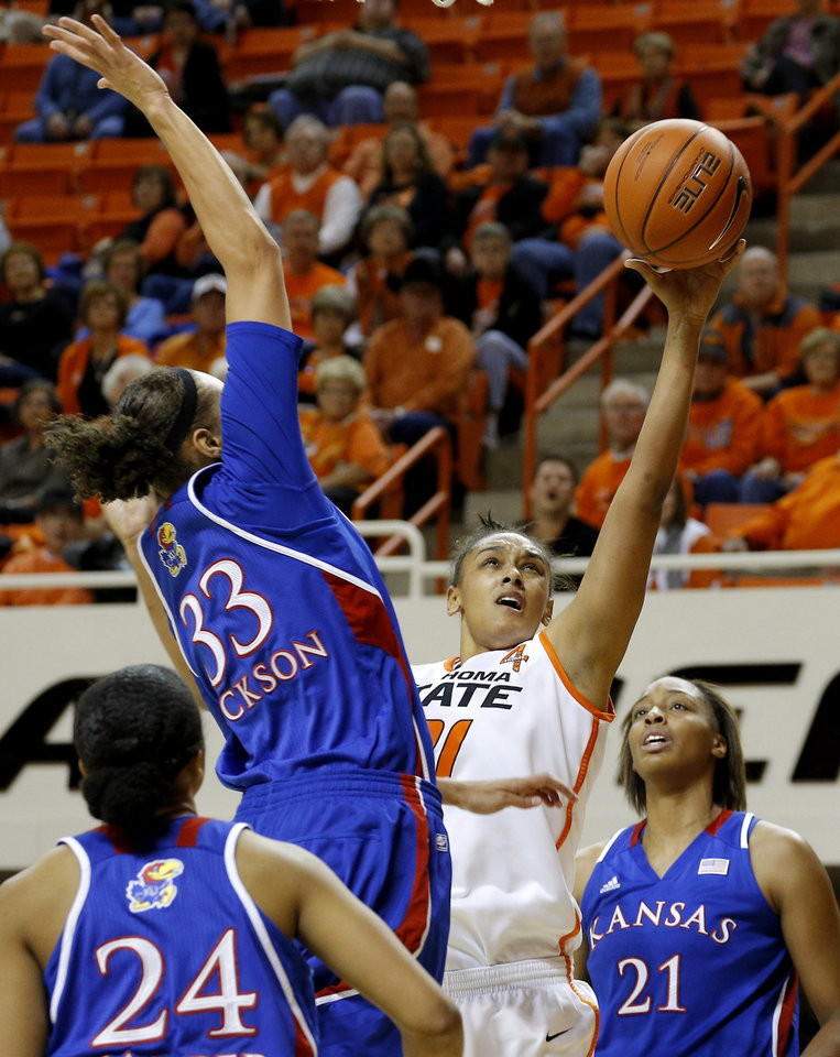 Photo - Oklahoma State's Kendra Suttles (31) shoots a basket between Kansas' CeCe Harper (24), Tania Jackson (33), and Carolyn Davis (21) during a women's college basketball game between Oklahoma State University (OSU) and Kansas at Gallagher-Iba Arena in Stillwater, Okla., Tuesday, Jan. 8, 2013. Oklahoma State won 76-59. Photo by Bryan Terry, The Oklahoman
