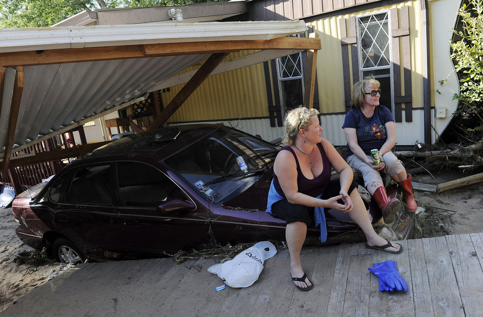 Photo - Jenna Brink, left, takes a break while clearing belongings from her flood-damaged trailer with her mother, Christine Brink, at the River Bend Mobile Home Park in Lyons, Colo., on Thursday, Sept. 19, 2013. Hundreds of evacuees were allowed past National Guard roadblocks Thursday to find a scene of tangled power lines, downed utility poles, and mud-caked homes and vehicles. (AP Photo/Chris Schneider)