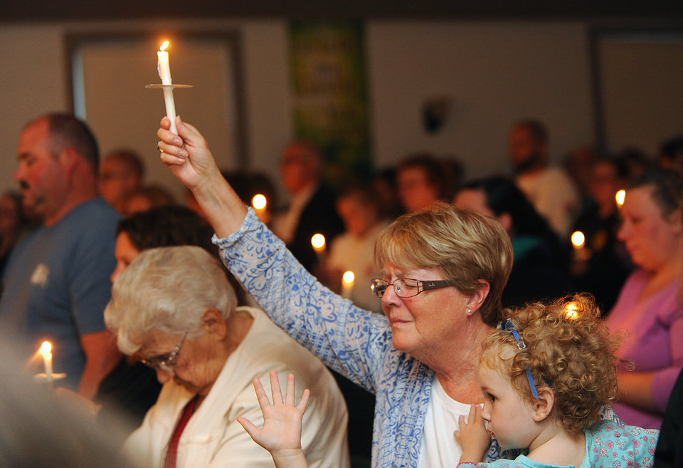 Photo - Lillian LaRose, Heuvelton, holds up a candle on Thursday, Aug. 14, 2014 during a candlelight vigil at the Cornerstone Wesleyan Church in Heuvelton for Fannie Miller, 12, and her sister Delila Miller, 6, who were still missing after being abducted Wednesday night at a farm stand near their home. (AP Photo/The Watertown Daily Times, Jason Hunter)