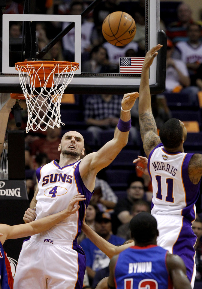 Photo -   Phoenix Suns' Marcin Gortat (4), of Poland, and Markieff Morris (11) battle for a rebound as Detroit Pistons' Will Bynum, front right, looks on in the first half of an NBA basketball game on Friday, Nov. 2, 2012, in Phoenix.(AP Photo/Ross D. Franklin)