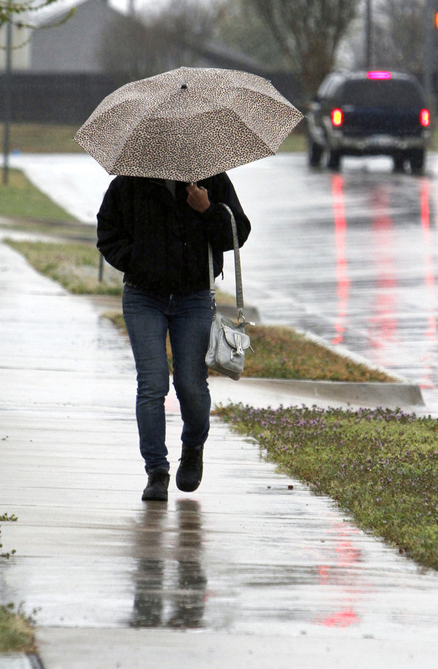 Walking in the rain in Edmond during Tuesday's wet weather. PHOTO BY PAUL HELLSTERN, THE OKLAHOMAN. <strong>PAUL HELLSTERN - THE OKLAHOMAN</strong>