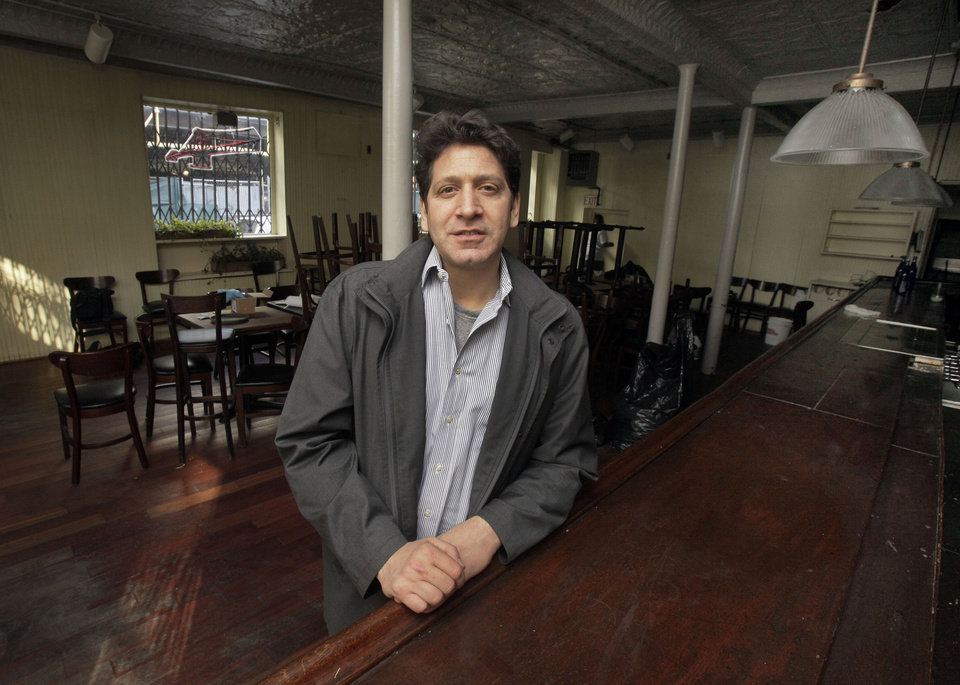 In this  Tuesday, Dec. 4, 2012, photo, Proprietor Adam Weprin, of the Bridge Cafe, in New York's South Street Seaport, poses for a photo at the restaurant's bar. Like many small business owners in the Northeast whose stores, restaurants, factories and offices were devastated or destroyed by the Oct. 29 storm, Weprin is hoping that federal, state and local officials will quickly come up with grants to help him rebuild and survive. (AP Photo/Richard Drew)