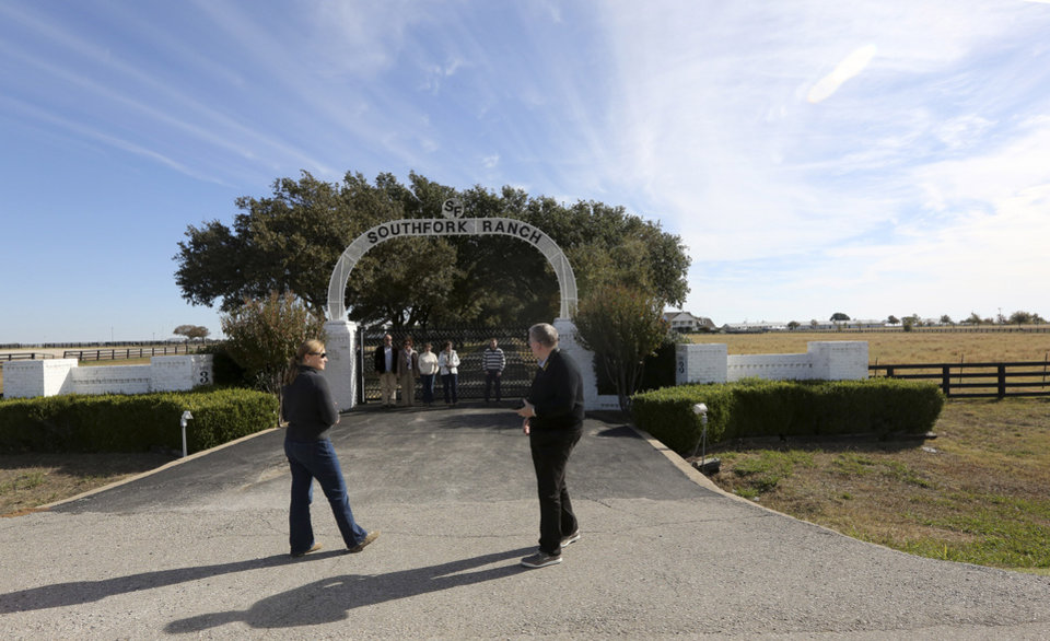 In this photo made Tuesday, Nov. 13, 2012, tourists line up fore a photo at the front gate of Southfork Ranch in Parker, Texas. Tourists have been flocking to Southfork Ranch since the early years of the classic series, which ran from 1978 to 1991. And a new �Dallas� starting its second season on TNT on Monday and the recent death of the show's star, Larry Hagman, who legendarily played conniving Texas oilman J.R. Ewing, have also spurred fans to visit. (AP Photo/LM Otero)