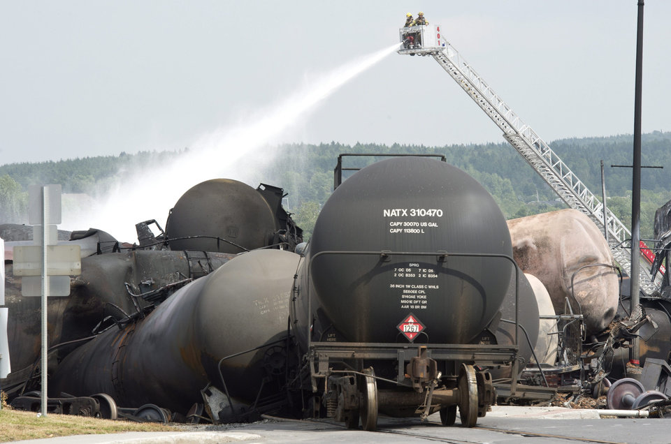 Photo - Fire fighters keep watering railway cars the day after a train derailed causing explosions of railway cars carrying crude oil Sunday, July 7, 2013, in Lac Megantic, Que. (AP Photo/The Canadian Press, Paul Chiasson)