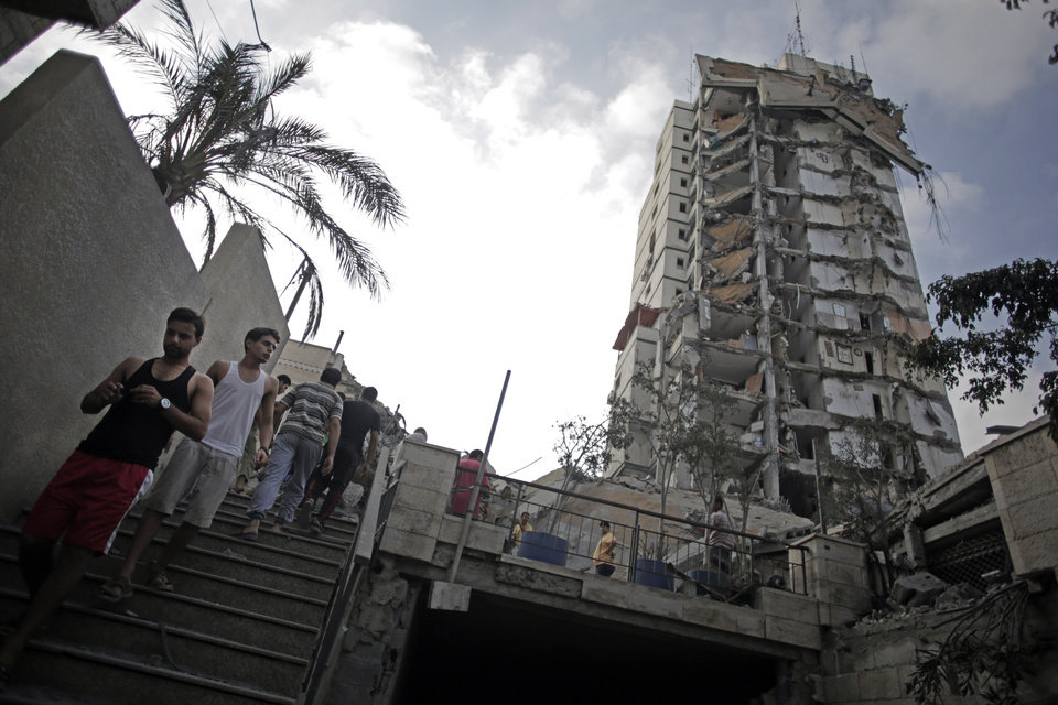 Photo - Palestinians walk near the damaged Italian Complex high-rise following several late night Israeli airstrikes in Gaza City, Tuesday, Aug. 26, 2014. Israel bombed two Gaza City high-rises with dozens of homes and shops Tuesday, collapsing the 15-story Basha Tower and severely damaging the Italian Complex in a further escalation in seven weeks of cross-border fighting with Hamas. (AP Photo/Khalil Hamra)