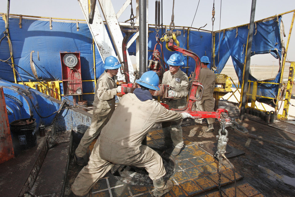 Photo - William Reed, Paul Tabarez and Justin Stanfill break a joint in drill pipe is pulled on a SandRidge oil drilling rig Oct. 18 near Medford.  Photo By David McDaniel/The Oklahoman