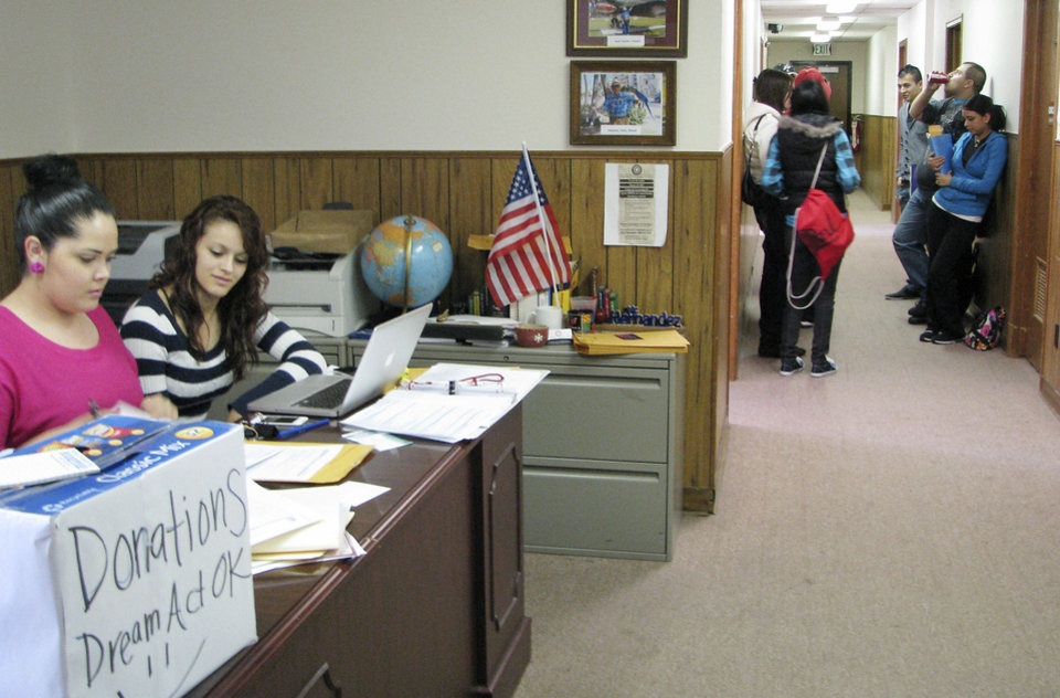 Deisy Escalera and Areli Carrillo sit at a desk to check in arrivals for a clinic to help immigrants apply for a program allowing them to possibly stay and work in the United States on Saturday, Oct. 27,at Capitol Hill Community Center. <strong>Vallery Brown - The Oklahoman</strong>
