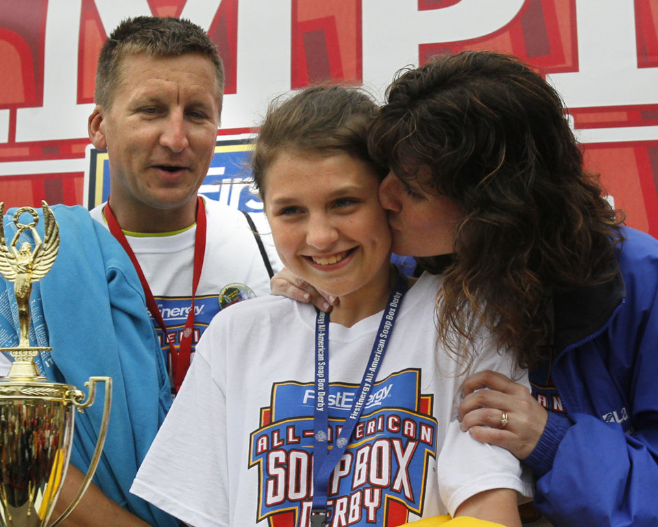 Macaila Ziolkowski, who won in Local Stock, is joined onstage by her parents, Donald and Heather, at the 76th All-American Soap Box Derby on Saturday, July 27, 2013, in Akron, Ohio. (AP Photo/Akron Beacon Journal, Paul Tople)