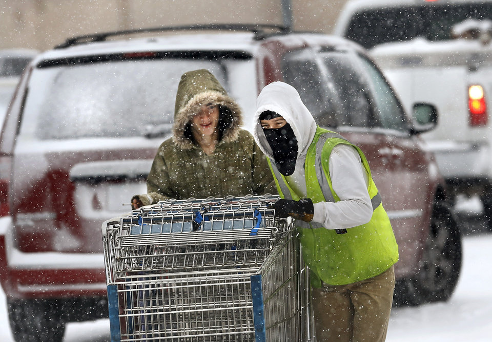 Photo - Workers push empty shopping carts to the front of Crest Foods in in Midwest City. Snow began falling in central Oklahoma around 7 Sunday morning, Feb. 2, 2014.   Photo by Jim Beckel, The Oklahoman