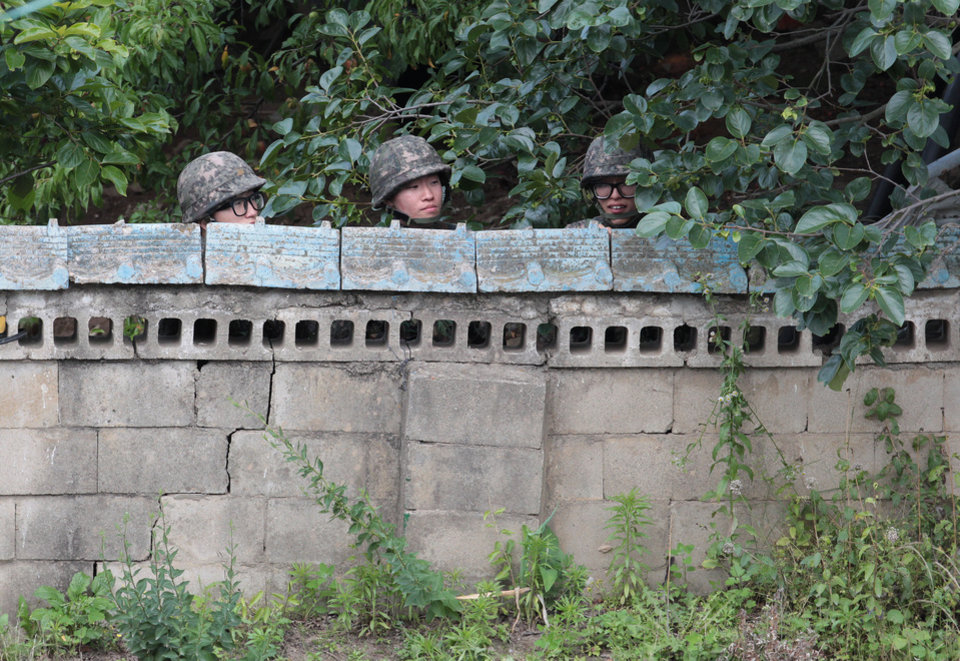 Photo - South Korean army soldiers hide behind a wall of a private house during a gunfight with a South Korean conscript soldier who is on the run after a shooting incident in Goseong, South Korea, Sunday, June 22, 2014. South Korean military authorities have surrounded a soldier who fled his border outpost after killing five comrades the day before and were trying to persuade him to surrender, a defense official said Sunday.(AP Photo/Ahn Young-joon)