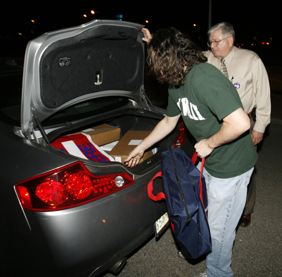 Photo - Election Board employee Mike Mullins removes poll equipment covering boxes of ballots as the first ballots arrive at the Cleveland County Election Board, on Tuesday, Nov. 4, 2008, in Norman, Okla.    Steve Sisney, The Oklahoman