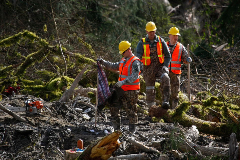 Photo - Members of the Washington State National Guard search through debris field for personal items and bodies, Wednesday, April 2, 2014, where workers continued to search through the mudslide area in Oso, Wash. (AP Photo/The Herald, Genna Martin)