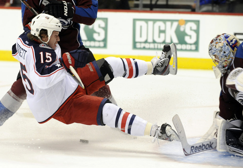 Photo - Columbus Blue Jackets right wing Derek Dorsett (15) is knocked off his skates as he shoots on Colorado Avalanche goalie Semyon Varlamov (1), of Russia, during the third period of an NHL hockey game, Thursday, Jan. 24, 2013, in Denver. The Avalanche won 4-0. (AP Photo/Jack Dempsey)