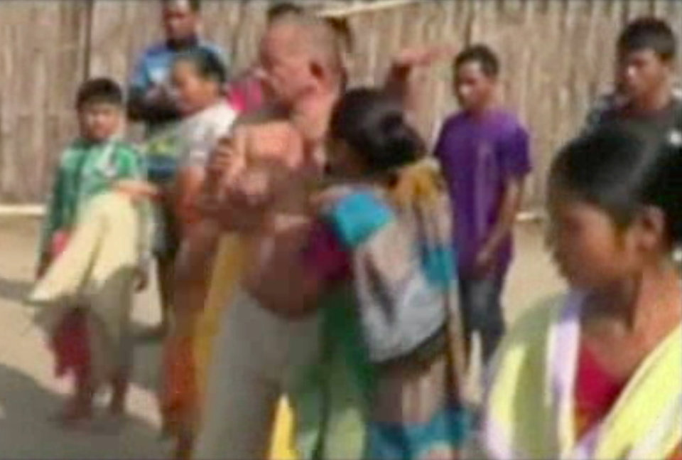 Photo - In this image taken from video obtained from Network 1 News and Information Syndicate (NNIS), which has been authenticated based on its contents and other AP reporting, Bikram Singh Brahma, center, a leader of India's ruling Congress party, is slapped by a woman in the village of Santipur, India, on Thursday, Jan. 3, 2013. Police said Brahma was visiting the village of Santipur on the Bhutan border when he entered a woman's house and raped her at 2 a.m. In a sign that attitudes might be changing since the rape of a 23-year-old woman in New Delhi, who died of severe internal injuries over the weekend, police have arrested Brahma. (AP Photo/NNIS)