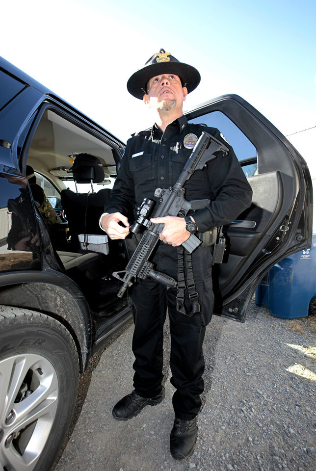 Photo - Kiowa Police Department Chief Tony Runyon check his weapon Friday before going out on patrol. Runyon said that U.S. 69 is a drug rout and he and his officers must be prepared. Photo by David McDaniel, The Oklahoman  David McDaniel