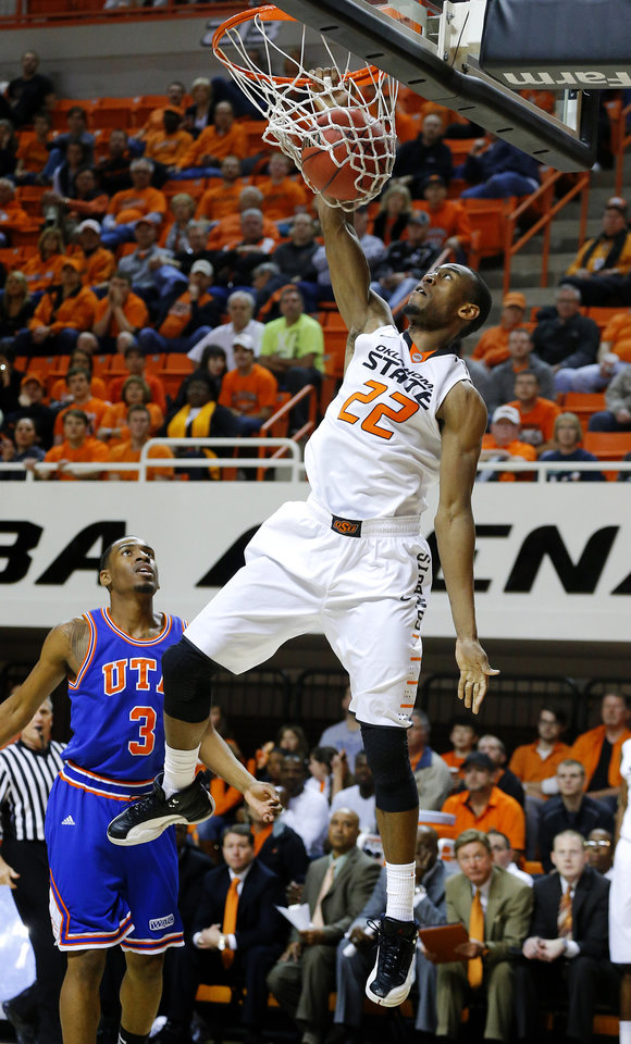 Photo - Oklahoma State's Markel Brown (22) dunks the ball as Texas-Arlington's Jamel Outler (3) watches during a college basketball game between Oklahoma State University and UT Arlington at Gallagher-Iba Arena in Stillwater, Okla., Wednesday, Dec. 19, 2012. Photo by Bryan Terry, The Oklahoman