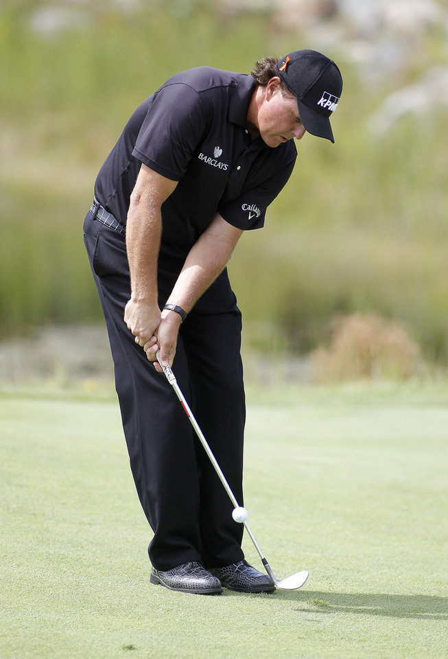 Photo - Phil Mickelson chips onto the second green during the first round of the Deutsche Bank Championship golf tournament in Norton, Mass., Friday, Aug. 29, 2014. (AP Photo/Stew Milne)