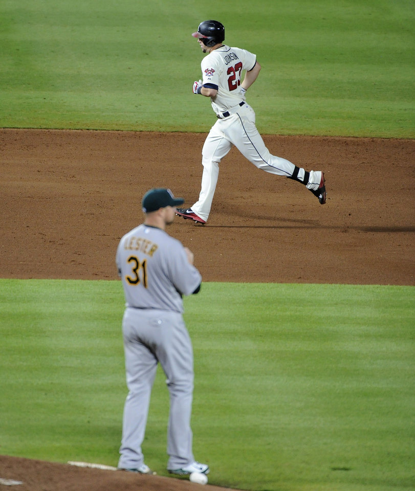 Photo - Atlanta Braves' Chris Johnson (23) rounds the bases behind Oakland Athletics starting pitcher Jon Lester (31) after Johnson's solo home run during the seventh inning of a baseball game Sunday, Aug. 17, 2014, in Atlanta. (AP Photo/David Tulis)