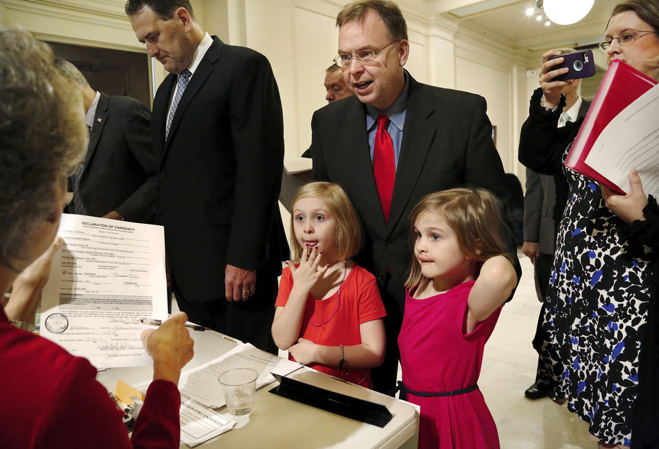 Photo -  Right:  Elizabeth, 7, and Sarah, 5, stand with their dad, Dr. Charles Mashek, as he files his papers with the Election Board on Wednesday at the state Capitol. He filed to be a candidate for a state Senate seat in District 28.  Jim Beckel -