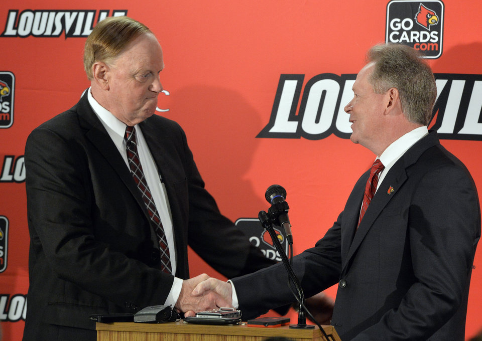 Photo - University of Louisville President Dr. James R. Ramsey, left, greets Bobby Petrino following he announcement of his hiring as the university's new NCAA college football coach Thursday, Jan. 9, 2014, at Papa John's Cardinal Stadium in Louisville, Ky. (AP Photo/Timothy D. Easley)