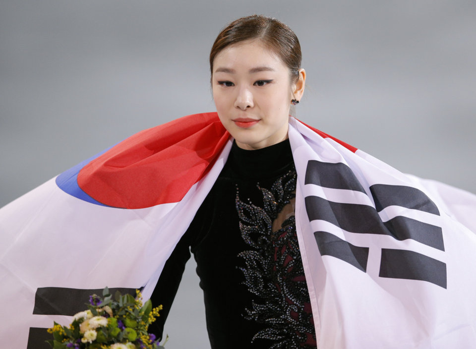 Photo - Yuna Kim of South Korea celebrates her second place with the national flag following the flower ceremony for the women's free skate figure skating finals at the Iceberg Skating Palace during the 2014 Winter Olympics, Thursday, Feb. 20, 2014, in Sochi, Russia. (AP Photo/Vadim Ghirda)