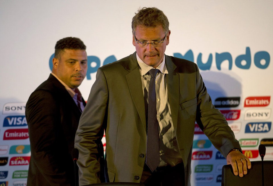 Photo - FIFA's secretary general Jerome Valcke, right, and former soccer player Ronaldo arrive to a press conference in Rio de Janeiro, Brazil, Thursday, Aug 22, 2013. FIFA's secretary general has floated an idea for a possible change to the World Cup bidding process in response to a spate of challenges in organizing next year's tournament in Brazil, which he says has