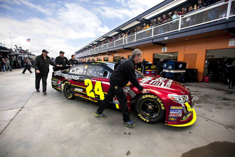 Pit crew members push Jeff Gordon's car for a template check before the start of qualifying for the NASCAR Sprint Cup Series auto race, Friday, March 8, 2013 in Las Vegas. (AP Photo/Julie Jacobson)