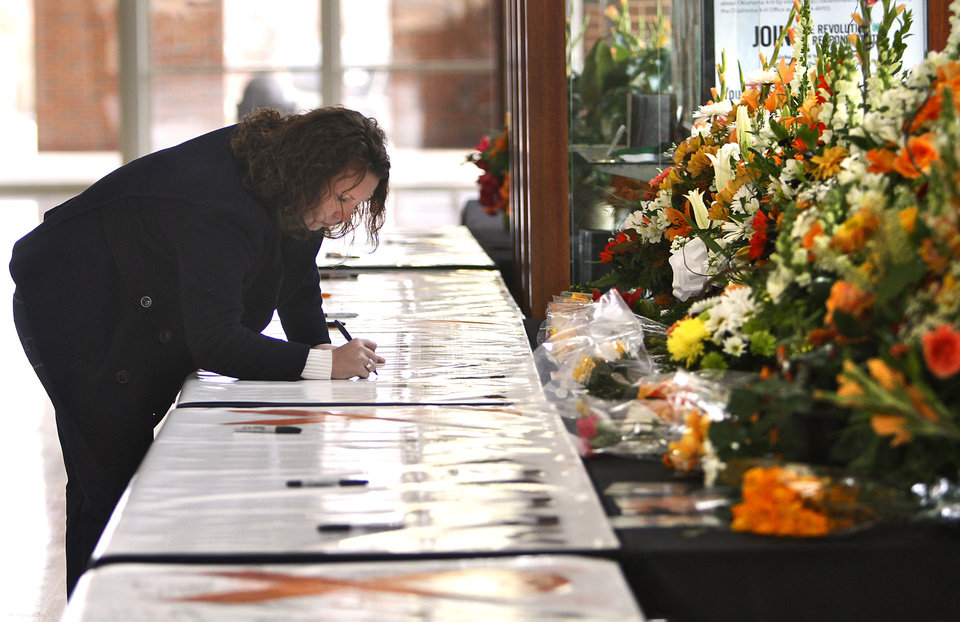 Photo - Ashley Boyd leaves a message on the memorial banner during the memorial service for Oklahoma State head basketball coach Kurt Budke and assistant coach Miranda Serna at Gallagher-Iba Arena on Monday, Nov. 21, 2011 in Stillwater, Okla. The two were killed in a plane crash along with former state senator Olin Branstetter and his wife Paula while on a recruiting trip in central Arkansas last Thursday. Photo by Chris Landsberger, The Oklahoman