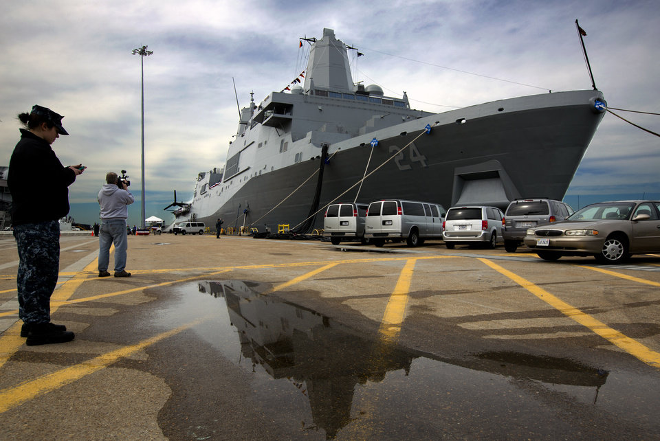 In this April 5, 2013 photo, the USS Arlington sits dock in its new home port at Norfolk Naval Station in Norfolk, Va. The Navy commissioned the USS Arlington in front of about 5,000 people in its new home port of Naval Station Norfolk. The amphibious transport dock is one of three ships named after 9/11 crash sites, and 200 pounds of steel salvaged from the Pentagon's wreckage have been forged into a pentagon to be put on a permanent display aboard the ship in a memorial room. The ship also has 184 gold stars throughout the ship in honor of those who died when American Airlines Flight 77 crashed into the Pentagon on Sept. 11, 2011. (AP Photo/The Virginian-Pilot, The' N. Pham)  MAGS OUT