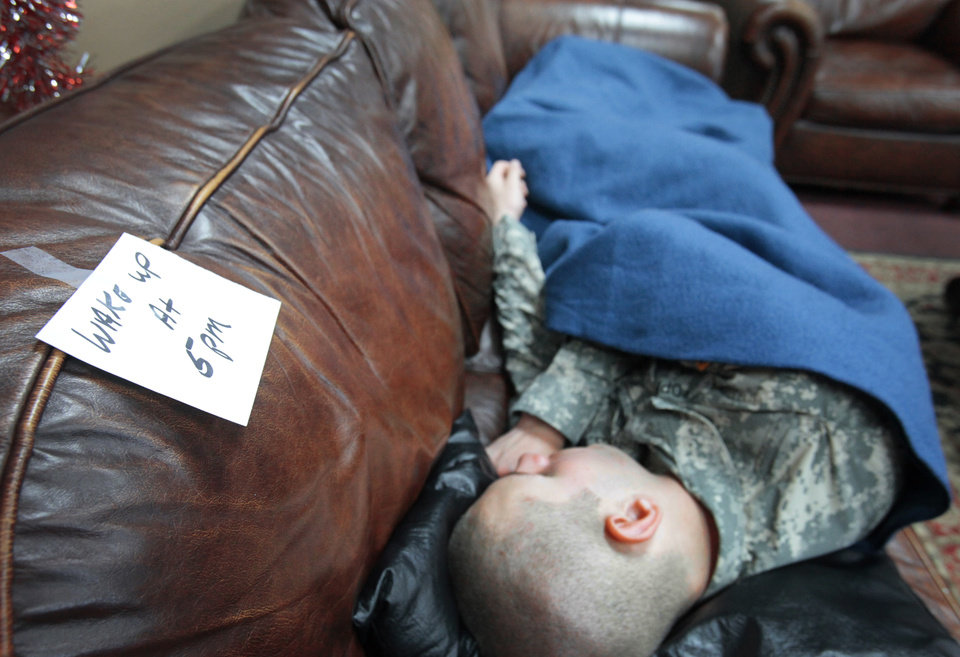 A solder sleeps on a couch in the YMCA Military Welcome center at Will Rogers World Airport with a note asking to be woken at 5:00 P.M., Friday, December 16 , 2011. Photo by David McDaniel, The Oklahoman