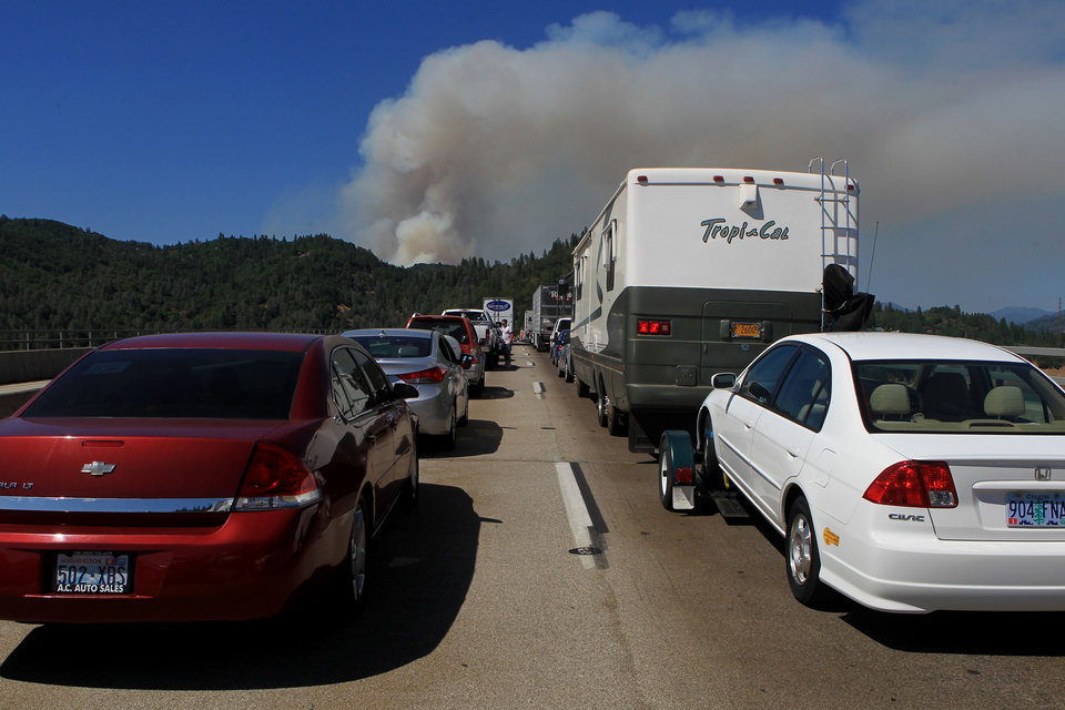 Northbound traffic comes to a standstill on the Pit River Bridge on Interstate 5 in Shasta County, Calif., as a plume of smoke rises Wednesday, Aug. 1, 2012, from the Salt Creek Fire. AP photo
