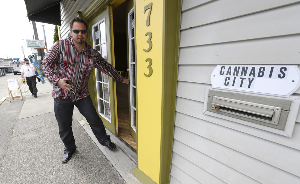 Photo - James Lathrop, left, the owner of the recreational marijuana store Cannabis City, walks out of his store, Monday, July 7, 2014, in Seattle. The store will be the first and only store in Seattle to initially sell recreational marijuana when legal sales begin on Tuesday, July 8, 2014. (AP Photo/Ted S. Warren)
