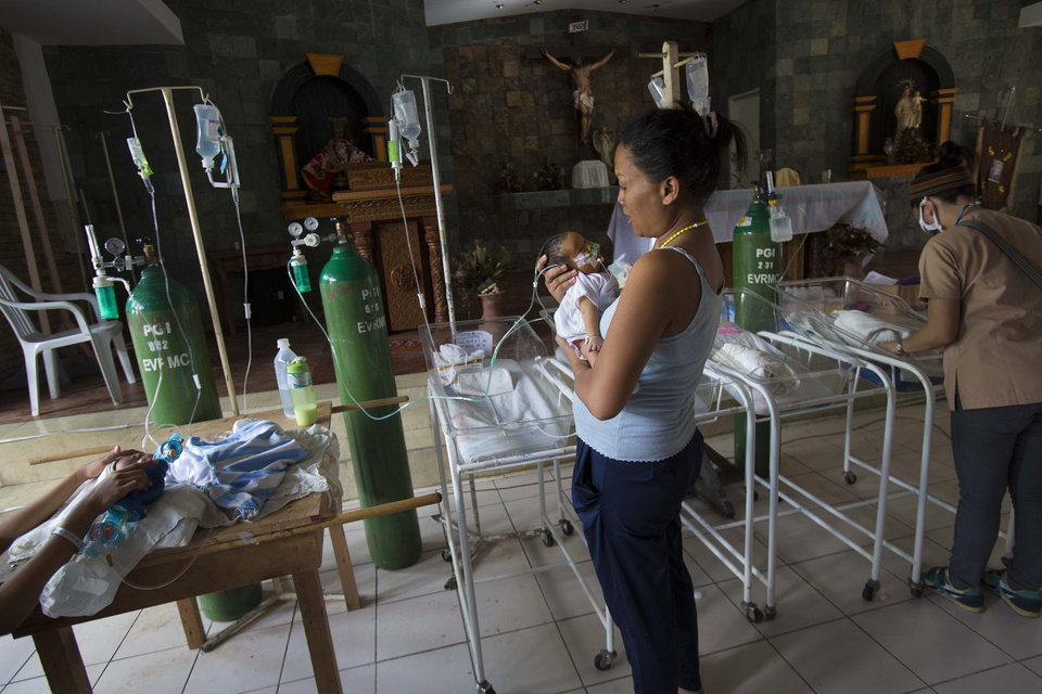Photo - Nanette Salutan holds her baby son Bernard in her arms in front of the altar of a Catholic chapel inside the Eastern Visayas Regional Medical Center in Tacloban, Philippines on Saturday Nov. 16, 2013. The chapel is now being used to care for infants after Typhoon Haiyan destroyed the original facility of the hospital. (AP Photo/David Guttenfelder)