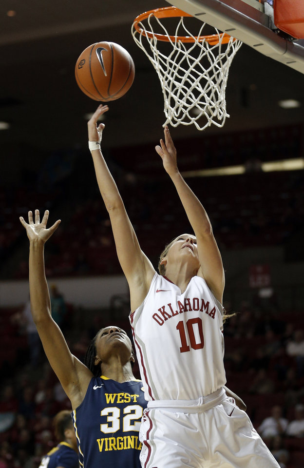 Photo - Oklahoma Morgan Hook (10) shoots a lay up in front of West Virginia Crystal Leary (32) during the women's basketball game between, University of Oklahoma and West Virginia, Thursday, Feb. 13, 2014, in Norman, Okla. Photo by Sarah Phipps, The Oklahoman