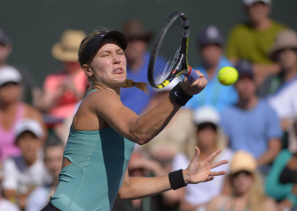 Photo - Eugenie Bouchard, of Canada, makes a return against Sara Errani, of Italy, in a match at the BNP Paribas Open tennis tournament on Sunday, March 9, 2014, in Indian Wells, Calif. Bouchard won the match 6-3, 6-3. (AP Photo/Mark J. Terrill)