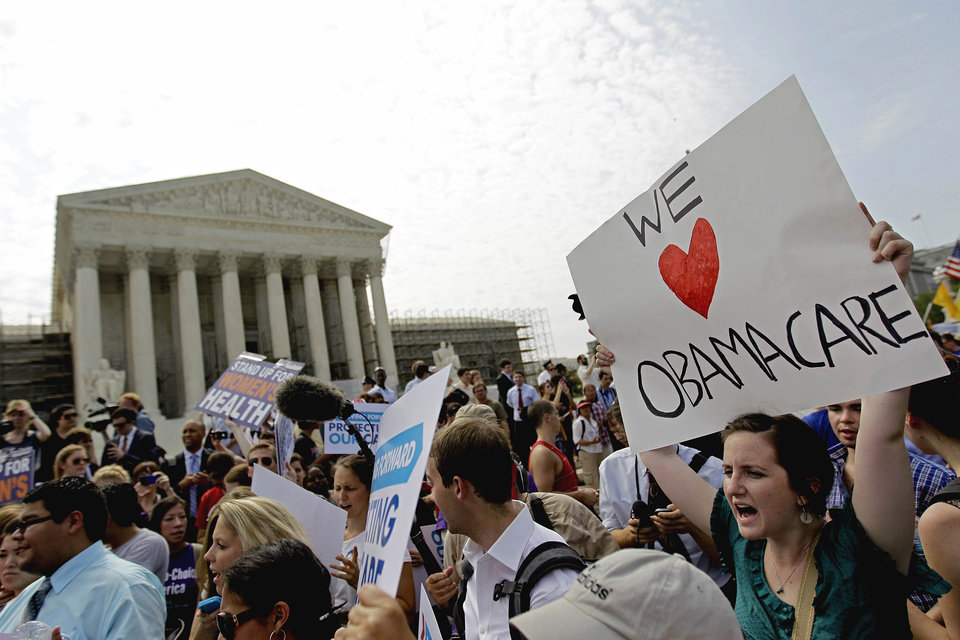Photo -   FILE - In this June 28, 2012 file photo, supporters of President Barack Obama's health care law celebrate outside the Supreme Court in Washington. It looks like a tax, smells like a tax, and the Supreme Court says it must be a tax. But politicians in both parties are squirming over how to define the Thing in President Barack Obama's health care law that requires people to pay up if they don't get health insurance. The problem for Obama is that, if the Thing is indeed a tax, he is by definition a raiser of taxes on the middle class, which he promised not to be. If that sounds like an opportunity for Republican presidential rival Mitt Romney, well, it's not that simple. (AP Photo/David Goldman, File)
