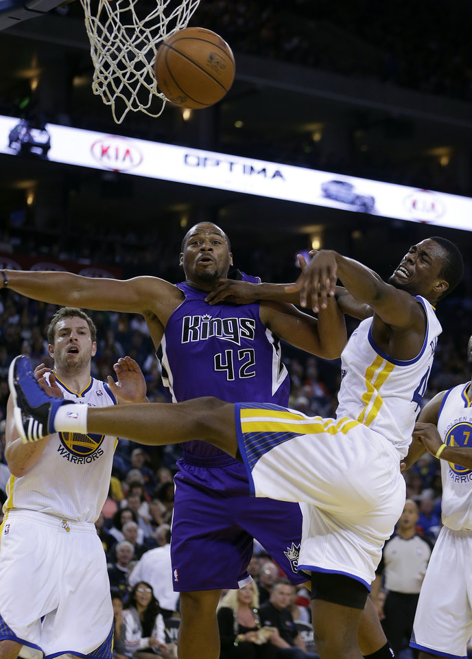 Sacramento Kings' Chuck Hayes (42) and Golden State Warriors' David Lee, left, and Harrison Barnes eye a loose ball during the first half of an NBA basketball game Wednesday, March 27, 2013, in Oakland, Calif. (AP Photo/Ben Margot)