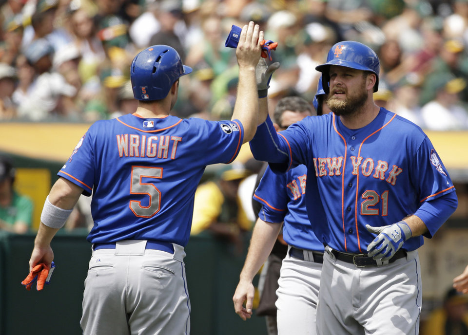 Photo - New York Mets' Lucas Duda, right, is greeted by teammate David Wright, left, after hitting a three run homer off Oakland Athletics starting pitcher Jeff Samardzija in the third inning of their interleague baseball game Wednesday, Aug. 20, 2014, in Oakland, Calif. (AP Photo/Eric Risberg)