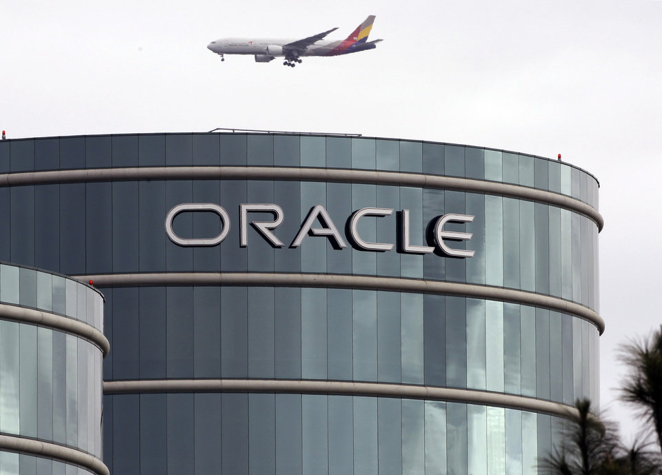 FILE - In this Tuesday, March 20, 2012, file photo, a plane flies over Oracle headquarters in Redwood City, Calif. Oracle\'s latest quarterly earnings rose 18 percent as companies splurged on more software and other technology toward the end of the year. (AP Photo/Paul Sakuma, File)