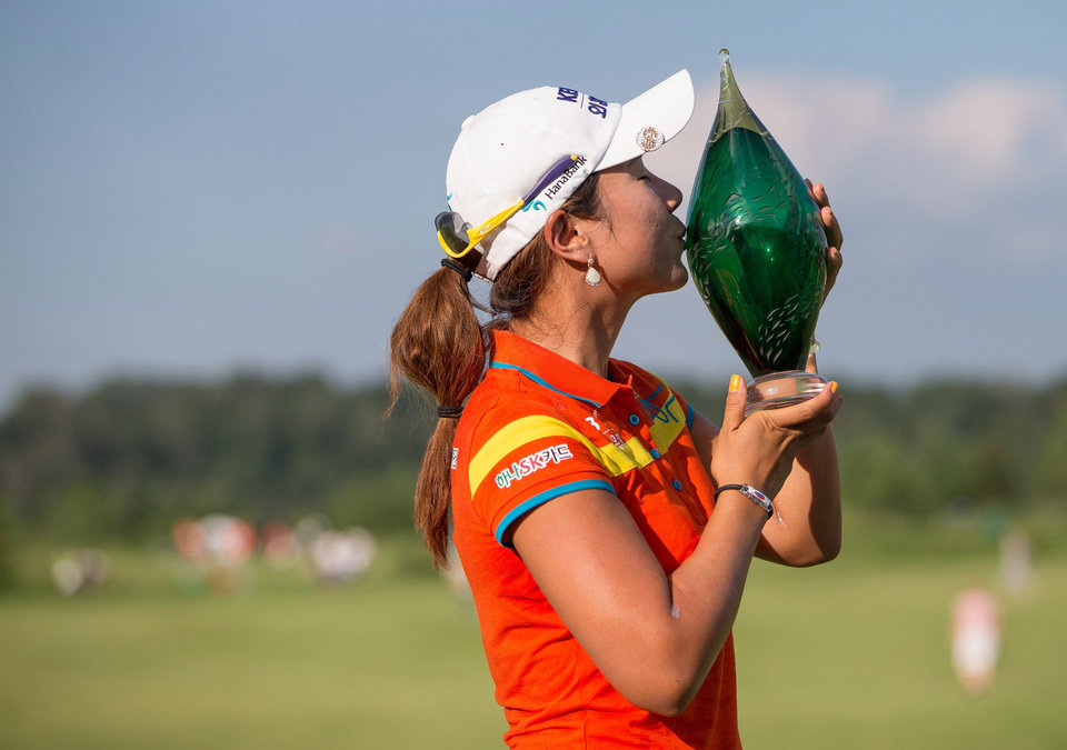 Photo - Hee Young Park, of South Korea, kisses the trophy following her victory on the third hole of a playoff in the Manulife Financial LPGA Classic golf tournament in Waterloo, Ontario, Sunday, July 14, 2013. (AP Photo/The Canadian Press, Geoff Robins)