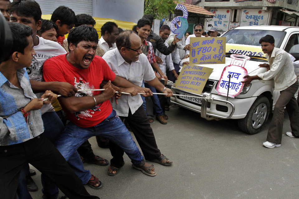 Photo -   Indian people pull a car by rope and shout slogans during a protest against the price hike in diesel and capping the number of subsidized cooking gas cylinders in Ahmadabad, India, Friday, Sept. 14, 2012. India's government is facing angry protests from its political allies as well as the opposition after it raised the price of diesel fuel in a bid to curb its ballooning fiscal deficit and also announced a reduction in cooking gas subsidies. The replica of cooking gas cylinder on the right reads as