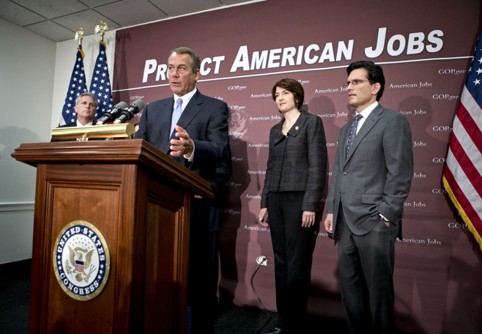 Photo - House Speaker John Boehner of Ohio, accompanied by the House GOP leadership, gestures as he speak to reporters on Capitol Hill in Washington, Wednesday, Dec. 5, 2012, following a closed-door GOP strategy session. From left are, House Majority Whip Kevin McCarthy of Calif., Boehner, Rep. Cathy McMorris Rodgers, R-Wash., and House Majority Leader Eric Cantor of Va.  (AP Photo/J. Scott Applewhite)