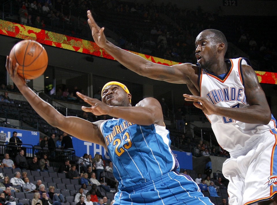 Photo - Devin Brown of the Hornets drives past Johan Petro of OklahomaCity for a basket during the NBA basketball game between the Oklahoma City Thunder and the New Orleans Hornets at the Ford Center in Oklahoma City on Friday, Nov. 21, 2008.   BY BRYAN TERRY, THE OKLAHOMAN
